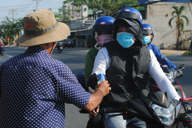 Man hands free water, tissues to people heading home for Tet reunion in Vietnam's Mekong Delta