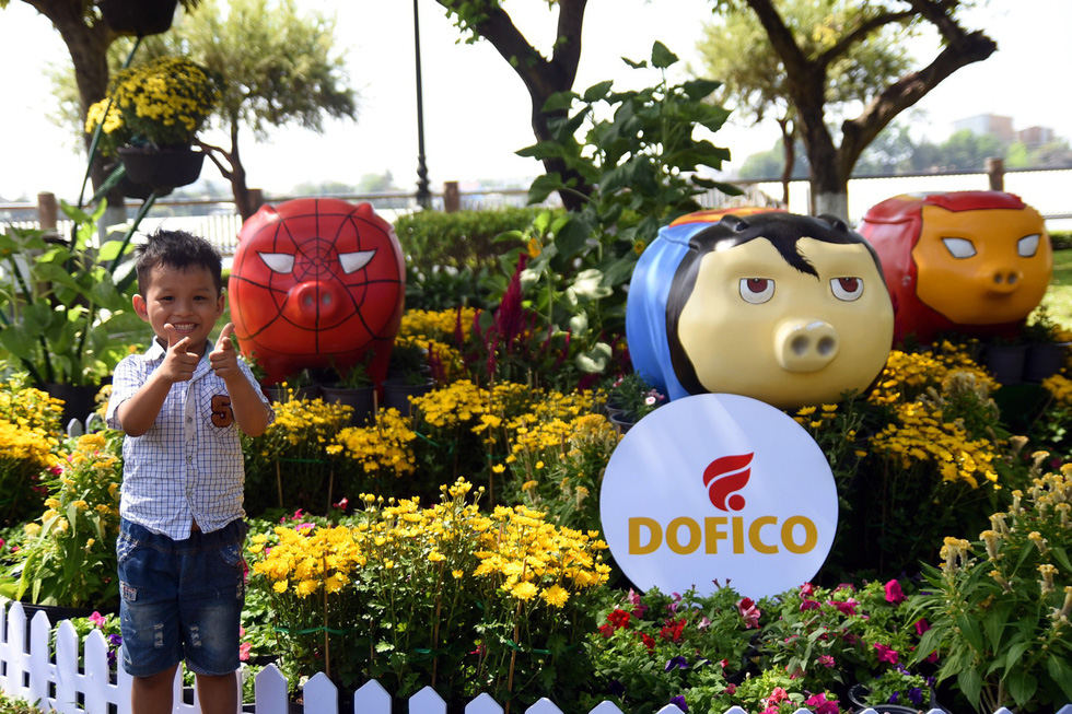 A little boy takes a photo with the 'superhero pig' statues. Photo: A Loc / Tuoi Tre