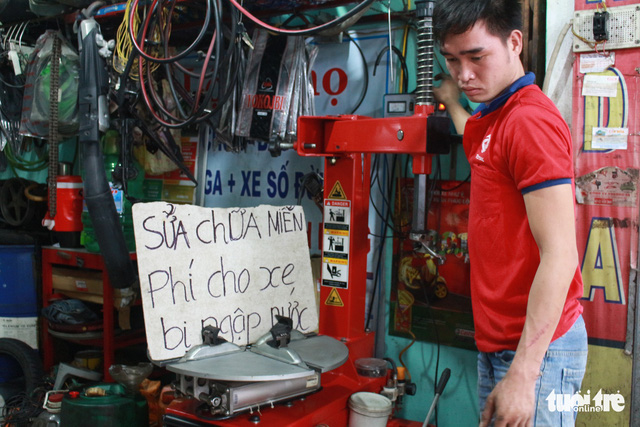 A mechanic stands beside a sign saying motorbike repair was offered free of charge during a rainstorm in Da Nang in December 2018. Photo: Doan Nhan / Tuoi Tre