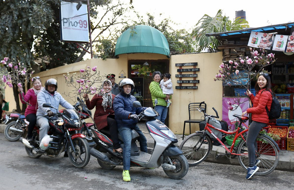 Huong Xuan (right) buys a branch of magnolias to decorate her house for Tet. Photo: Hiep Tran