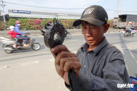 Nguyen Van Thanh shows a magnet with pointed objects that he collects along a portion of Vietnam's lifeline National Route 1 in Ho Chi Minh City, Vietnam. Photo: Le Phan / Tuoi Tre