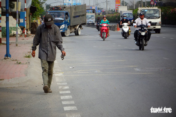Vietnamese scrap dealer picks up pointed objects on national highway to prevent accidents