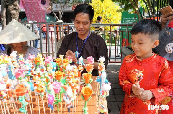 A young boy is fascinated by toy figurines at the flower street. Photo: Tuyet Kieu / Tuoi Tre