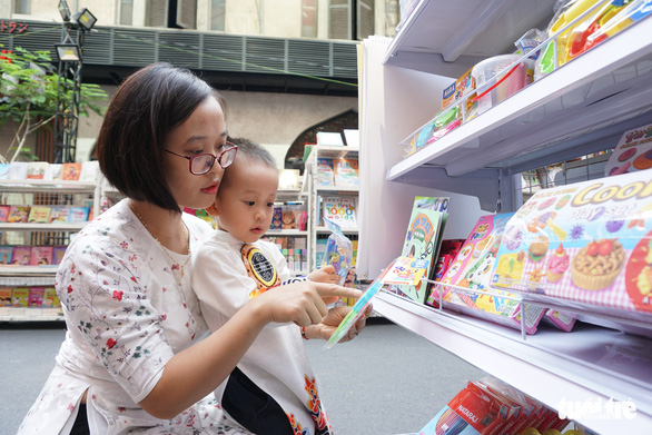 A mother browses for a book for her two-year-old son. Photo: Tuyet Kieu / Tuoi Tre