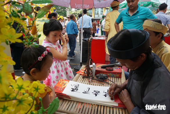 Young kids watch a calligrapher perform. Photo: Tuyet Kieu / Tuoi Tre