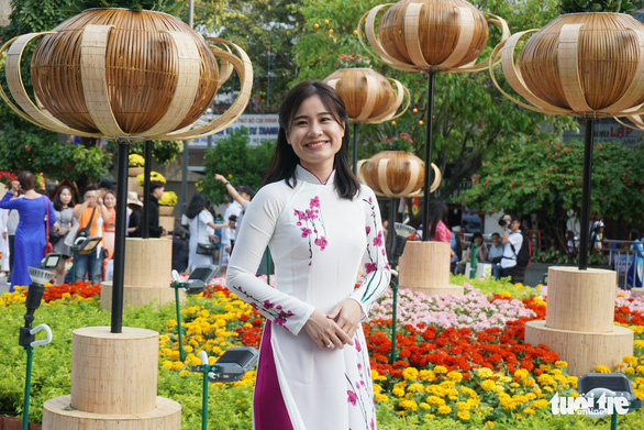 A woman dressed in 'ao dai' poses for a photo at the flower street. Photo: Tuyet Kieu / Tuoi Tre