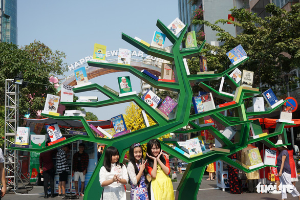 Young visitors take a photo at the book street. Photo: Tuyet Kieu / Tuoi Tre