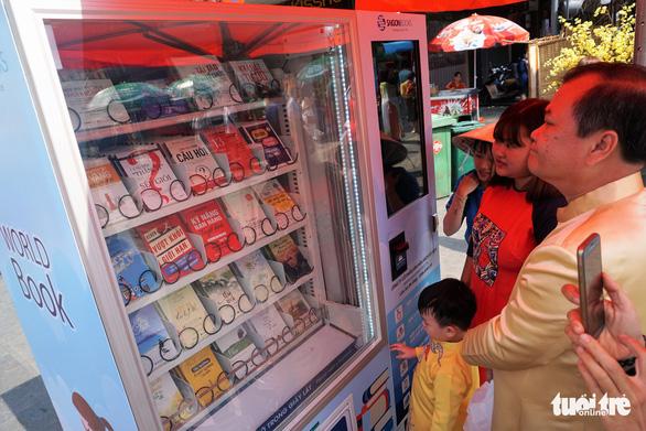 Visitors check out a book vending machine. Photo: Tuyet Kieu / Tuoi Tre