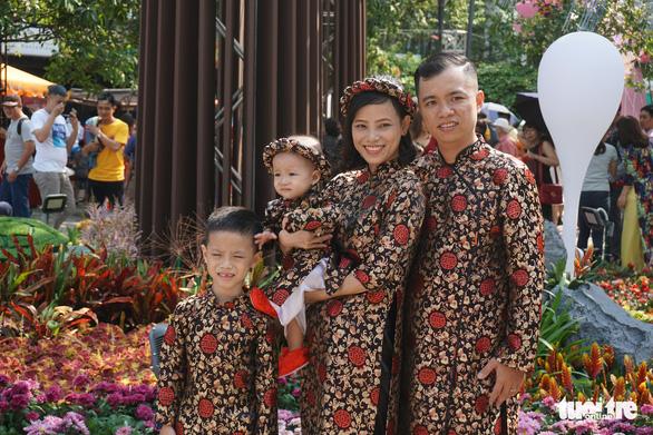 People take a group photo along Nguyen Hue Flower Street. Photo: Tuyet Kieu / Tuoi Tre