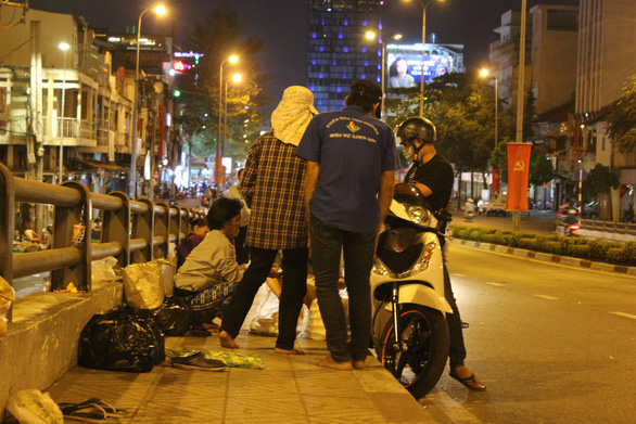 As a generous man stops his motorbike to distribute gifts to beggars for lunar new year, many beggars quickly gather. Photo: My Lang / Tuoi Tre
