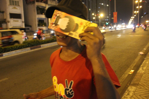 A man is happy as he has been given a lucky money envelope by a good-hearted passerby. Photo: My Lang / Tuoi Tre