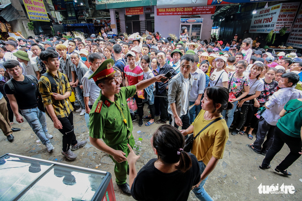A police officer instructs visitors to get in line at the Huong Pagoda in rural Hanoi on February 10, 2019. Photo: Nam Tran / Tuoi Tre