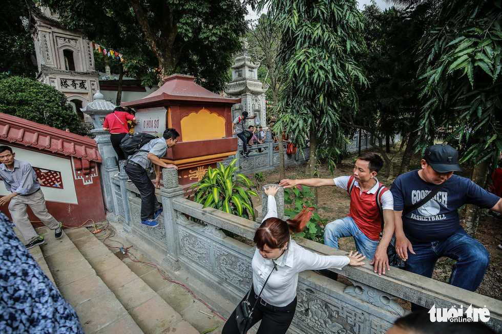 Visitors climb over a fence to cut in line at the Huong Pagoda in rural Hanoi on February 10, 2019. Photo: Nam Tran / Tuoi Tre