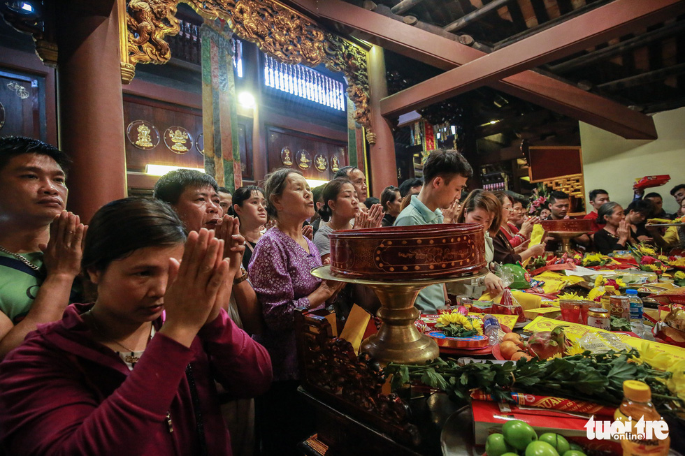 Visitors offer prayers before an altar inside the Huong Pagoda in rural Hanoi on February 10, 2019. Photo: Nam Tran / Tuoi Tre