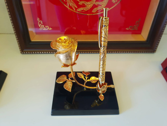 A combo of a gilded rose and a gilded pen. Photo: Bong Mai / Tuoi Tre