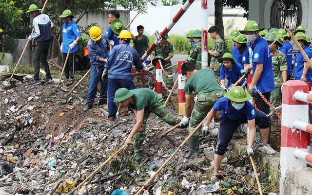 Volunteers of Ho Chi Minh City helping the workers taking out the garbage stuck in channels. Photo: Q. Ng. / Tuoi Tre