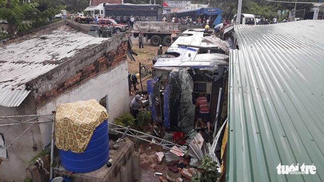 An overturned passenger bus lies next to house rubble after one of its tires goes flat in Nha Trang City, south-central Vietnam, February 14, 2019. Photo: Dinh Cuong / Tuoi Tre