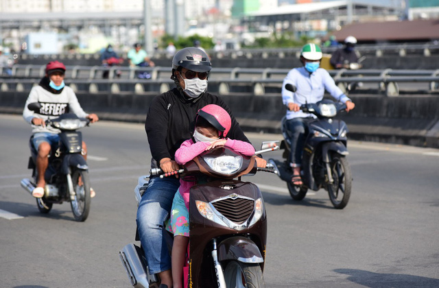 Commuters travel under the heat on Pham Van Dong Street in Binh Thanh District. Photo: Duyen Phan / Tuoi Tre