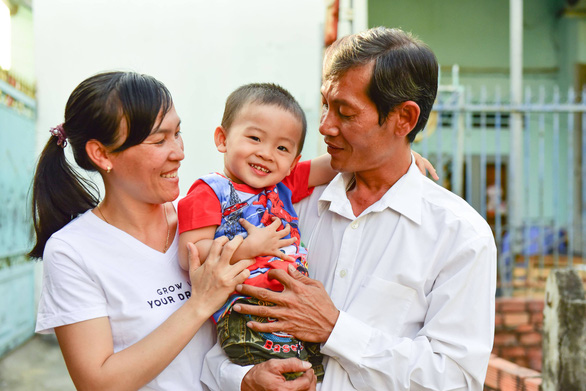 A couple plays with their child born through in vitro fertilization sponsored by a program that supports infertile couples in Vietnam. Photo: Huu Thuan / Tuoi Tre