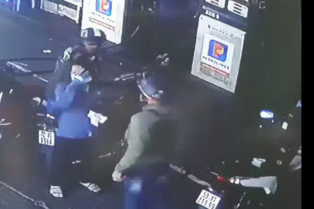 Attendant Nguyen Thi H. (in blue) covers her face with a hand after a customer punches her when his tank has overflowed, at a gas station in Ba Ria-Vung Tau Province, southern Vietnam, February 19, 2019, in this screenshot taken from CCTV footage.
