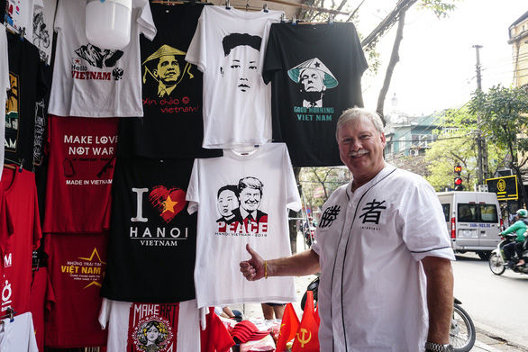 Michael Landa, an American tourist, poses for a photo in front of souvenir T-shirts that mark the DPRK-USA Hanoi Summit in Vietnam. Photo: Nguyen Hien / Tuoi Tre