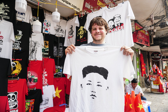 A tourist poses for a photo in front of souvenir T-shirts that mark the DPRK-USA Hanoi Summit in Vietnam. Photo: Nguyen Hien / Tuoi Tre