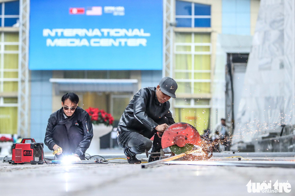 Welders assemble metal frames used for affixing posters inside the international media center for the DPRK-USA Hanoi Summit. Photo: Nguyen Khanh / Tuoi Tre