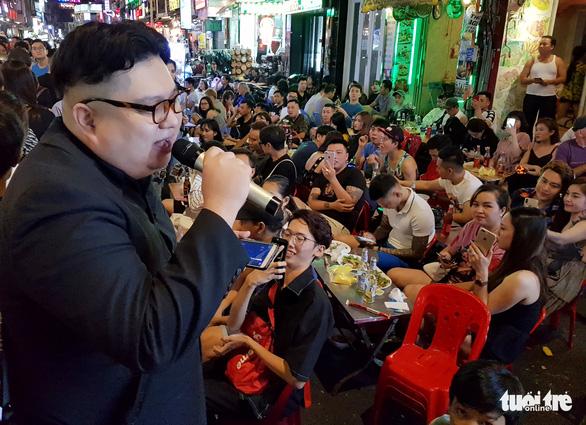 Dragon Kim sings to people on Bui Vien Walking Street. Photo: Ngoc Hien / Tuoi Tre