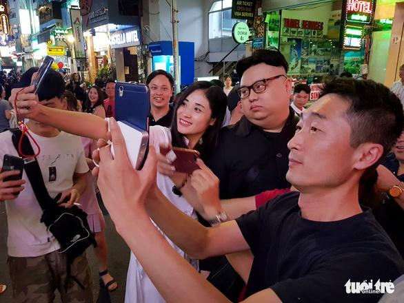 People take selfies with Dragon Kim. Photo: Ngoc Hien / Tuoi Tre