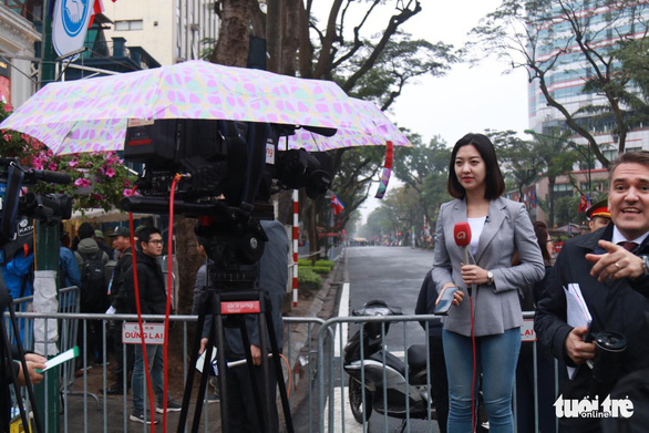 A reporter works in front of the Melia Hanoi Hotel despite the rainy weather. Photo: Minh Khoi / Tuoi Tre