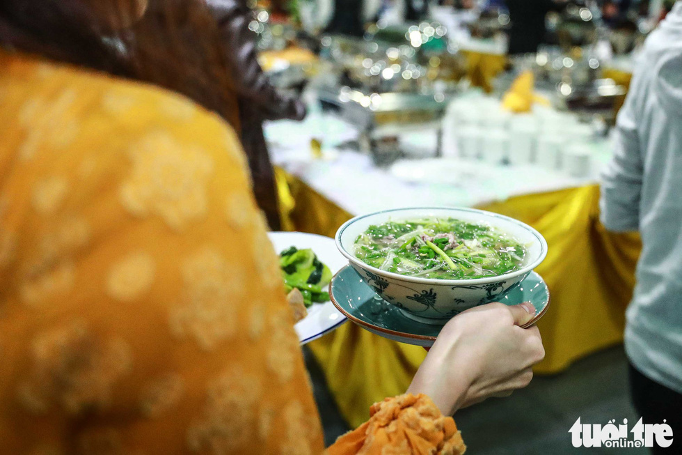 A reporter carries a bowl of 'pho.' Photo: Nguyen Khanh / Tuoi Tre