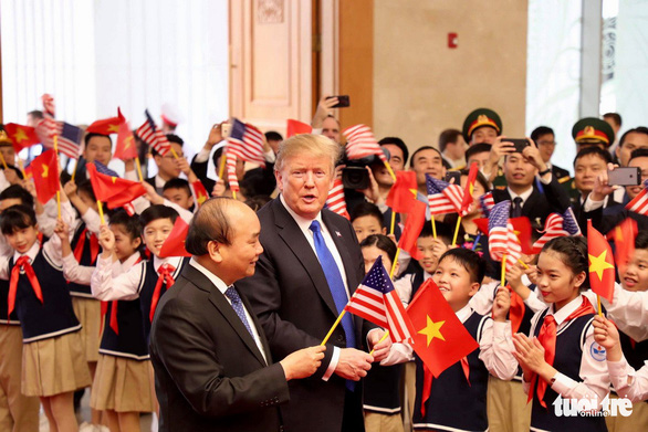 The two leaders wave national flags along with a group of Vietnamese children. Photo: Nguyen Khanh / Tuoi Tre