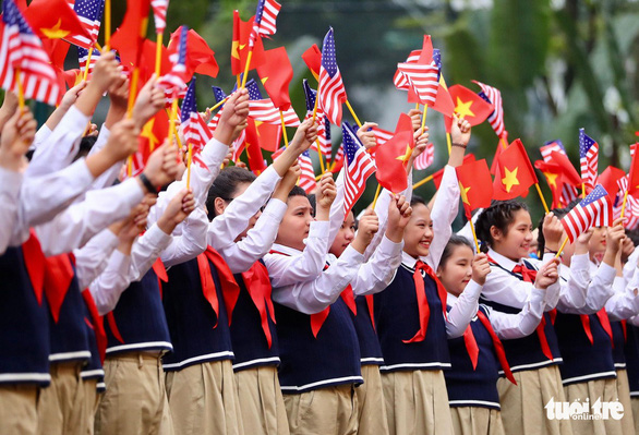 Vietnamese students wave the two country's flags in front of the Presidential Palace in Hanoi. Nguyen Khanh / Tuoi Tre