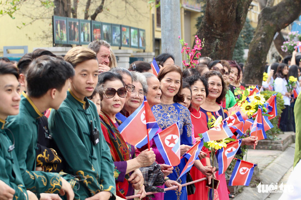 Hanoi residents welcome Chairman Kim on Ly Thuong Kiet Street as his motorcade travel from the hotel to the Presidential Palace. Photo: Chi Tue / Tuoi Tre