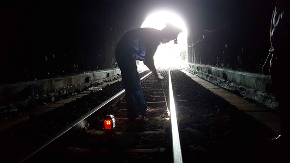 A patroller is tightening a loose screw on a tunnel track. Photo: Thai Loc / Tuoi Tre