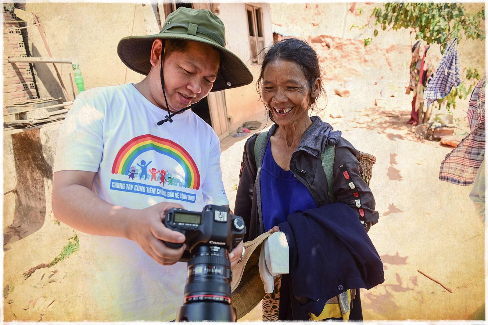 Ho Vinh Thang shows his photos of the trip to a local. Photo: Tuoi Tre