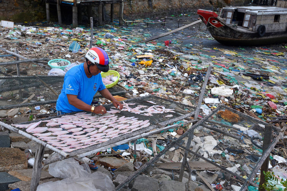 A resident dries fish on a trash-filled beach in Can Gio District, Ho Chi Minh City.