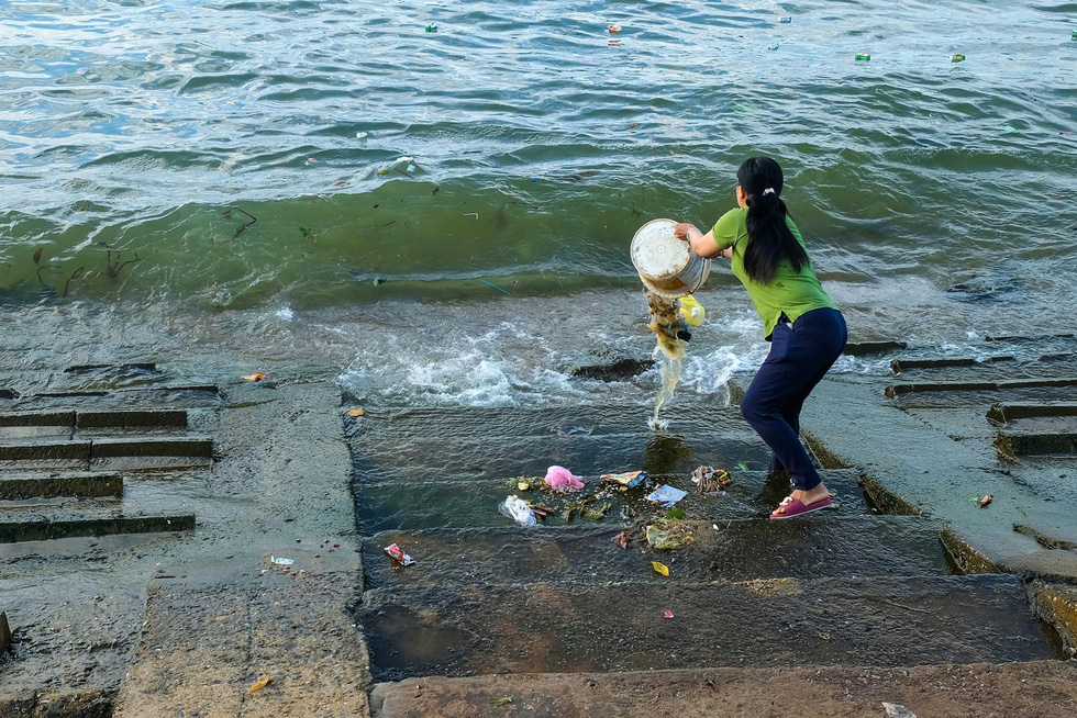 A woman dumps waste into the sea on Ly Son Island off south-central Quang Ngai Province.