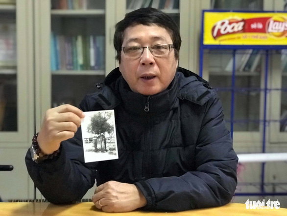 Tran Nhat Chinh holds a photo taken with his student Ri Ho Jun 35 years ago. Photo: Ngoc Ha / Tuoi Tre