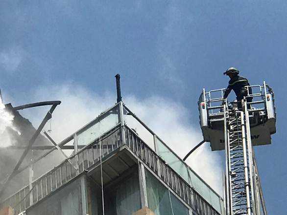 A firefighter works on a ladder truck. Photo: Le Phan / Tuoi Tre