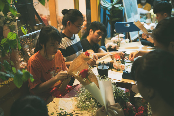 Volunteers wrap small bouquets of flowers to give them to women on the streets in Ho Chi Minh City on March 8, 2019. Photo: Chau Tuan / Tuoi Tre