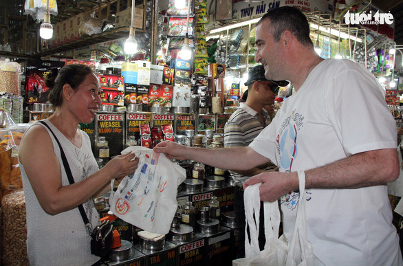 Representative from the Consulate General of Canada gives a recycled bag to a seller at the market. Photo: Quang Khai / Tuoi Tre