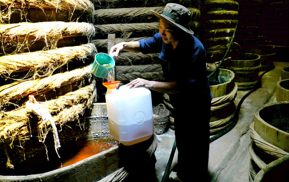 A worker cans fish sauce after fermentation in Phan Thiet City, south-central Vietnam. Photo: Nguyen Cong Thanh / Tuoi Tre
