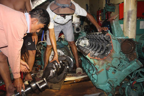 Fishermen remove engines from a steel-clad vessel for repair. Photo: Thai Thinh / Tuoi Tre