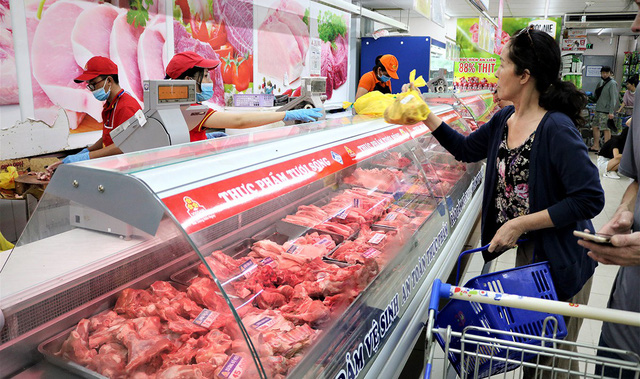 A woman buys pork at a supermarket in District 1, Ho Chi Minh City. Photo: Nguyet Nhi / Tuoi Tre