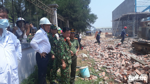 A government official and police watch the effort to find laborers in the rubble of collapsed wall in Vinh Long Province, southern Vietnam, March 15, 2019. Photo: Thanh Nam / Tuoi Tre
