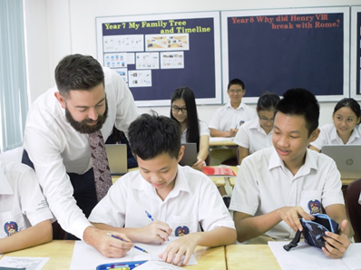 Mr Bradley Minchin (left) with his students in a history class.
