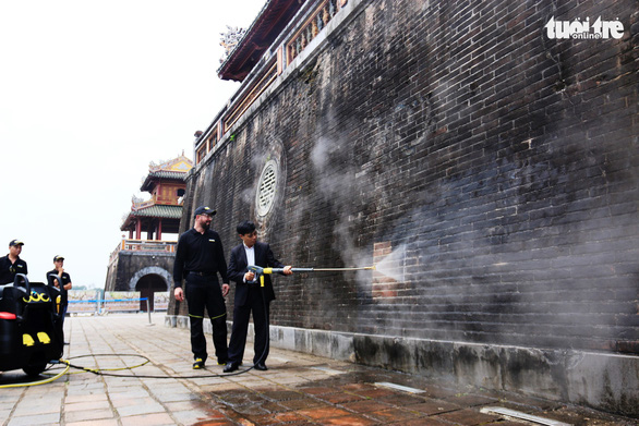 A foreign expert gives instructions on cleaning the wall of the Ngo Mon by steam. Photo: Nhat Linh / Tuoi Tre