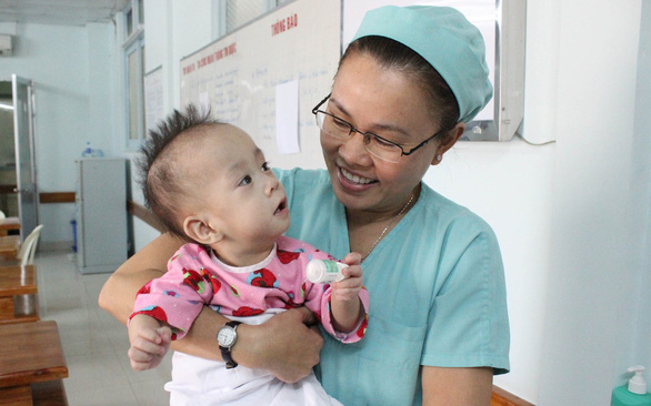 Phi Long being held by one of the nurses two months after the surgery. Photo: My Lang / Tuoi Tre