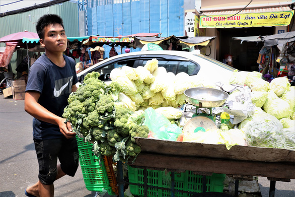 Pham Viet Quy and his vegetable at the makeshift market